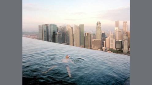 Homem flutua na piscina no 57º andar do hotel Marina Bay Sands Hotel, com os prédios do distrito financeiro de Singapura no fundo